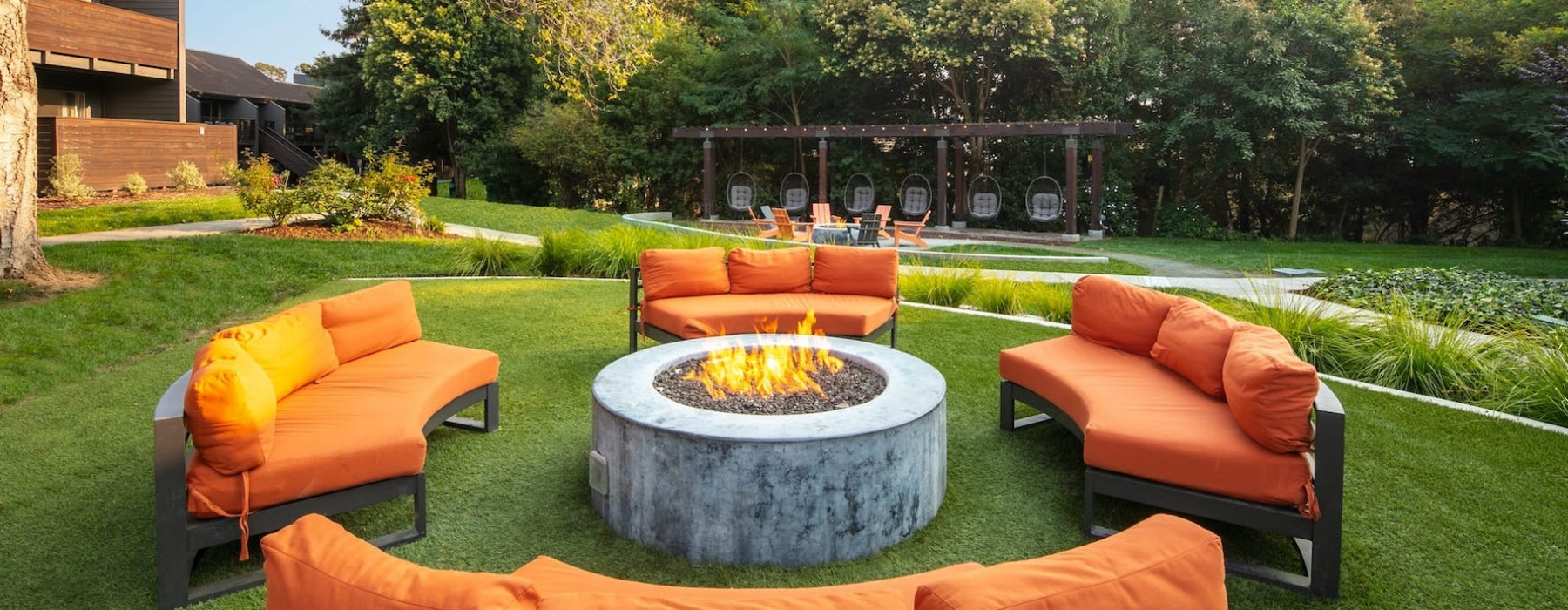 spacious seating around a firepit in a large outdoor lounge area
