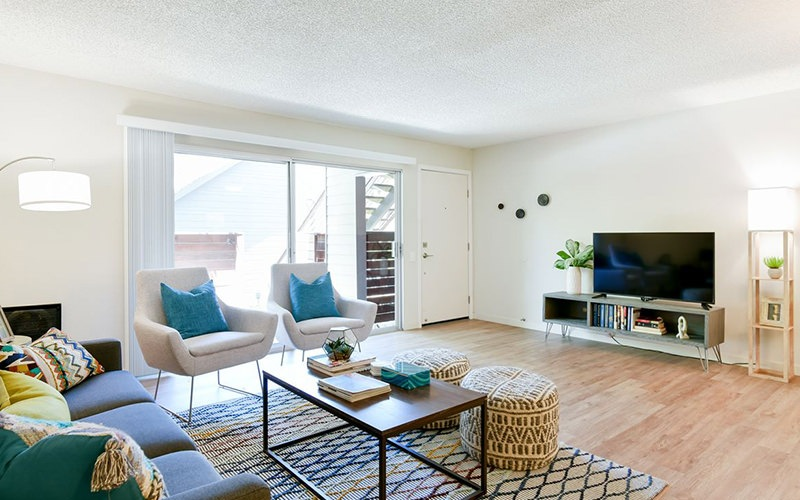 Spacious and well lit living room with wood floors and an open floor plan with access to the kitchen.
